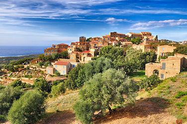 Vue sur le village vacances Corse de Pigna entouré d'arbre et niché sur des collines