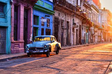 Rue colorée à Cuba avec voiture garée