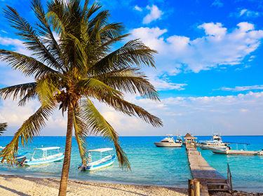 plage de sable vue mer ponton et bateau, palmiers sur la Riviera Maya au Mexique